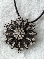 "2"" round snowflake shaped black with Swarovski crystals on a black leather necklace."