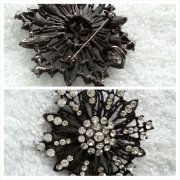 "2"" Round black snowflake shaped pin/necklace with Swarovski crystals. Back details the pin and clasp for necklace strand."