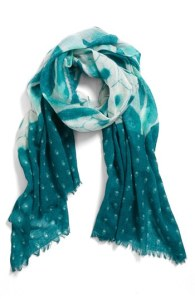 Hinge Patchwork Print Scarf. Bold patterns intensify the graphic appeal of a gauzy, fringe-trimmed scarf. 28 inches wide by 76 inches long. 100 percent wool. Colors are shades of teal and white.