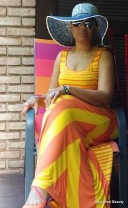 Me sitting wearing my floppy hat, aviators, orange/yellow maxi dress