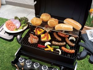 Grill with hamburgers, hotdogs, veggies and buns