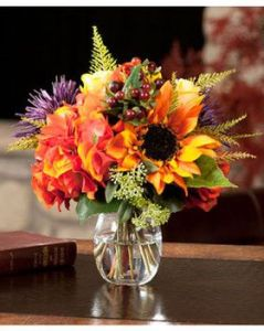 Colorful bouquet of Autumn flowers in a clear vase. shades of yellow, orange, green, brown, red and a little purple.