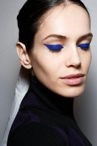 3 quarter view of a woman's face with dark blue (almost navy) eye shadow wings that extend beyond the outer part of the eye.