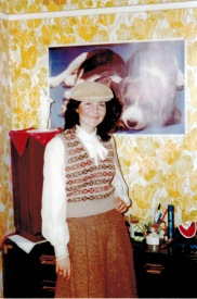 Picture of Maribel wearing a pleated skirt, blouse that ties at the neck, patterned sweater vest and a tam. Colored coordinated in shades of tan, oranges & browns
