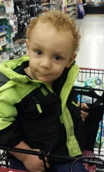 Picture of Orion with his first haircut sitting in a shopping cart showing off his pretty red curls at the store.