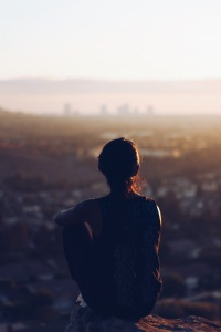 Solitary woman sitting on a  hill in the sunset  overlooking a vast valley. Photo Courtesy of Chris Sardegna Found on Unsplash.com