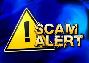 Image of a yellow triangle with exclamation in it denoting a warning and scam alert on top.