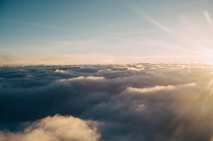 Photo of clouds taken from a plane, The sky is blue and there are golden rays of sunshine in the upper right corner of the photo. The clouds are so think they look like you could literally leap out up on them. Photo by Liane Metzler of Unsplash