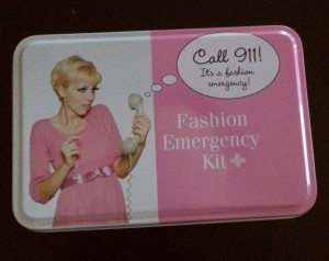 """Fashion Emergency Kit in a pink and white square tin with photo of a woman holding a phone and a speech bubble saying """"Call 911 its a fashion emergency"""""""