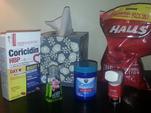 Picture of my box of tissue, bag of Halls cough drops, Vicks Vapor Rub, inhaler, and oral decongestant