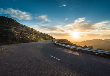 Photo of a winding mountain highway headed towards a golden sunset with a blue sky with puffy white clouds by Joshua Sortino
