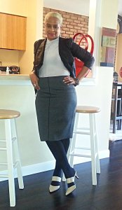 Front facing pose in gray top & skirt, black moto jacket and taupe heels