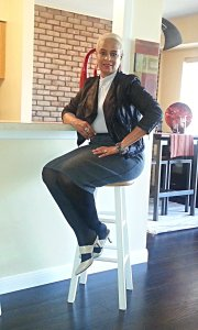 3 quarter seated pose in gray top & skirt, black moto jacket and taupe heels