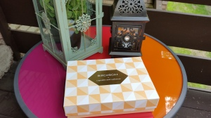 Birchbox on a round accent table with two decorative lanterns in the background.