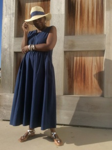 Navy blue midi dress is sleveless with an empireist. Natural straw  flappy hat has a navy band that complements the dress. The silver sandals are thong styled with straps that wrap around the ankles.  A beautifully pulled together look.