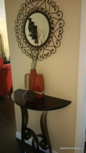 In my hallway I have a Tulip accent table (the metal base is tulip shaped and the wooden top is a half circle. Above the table is a circular mirror surrounded with mettal scrollwork. On top of the table is a squarish vase that holds twigs and in front of the vase is a wicker ball.