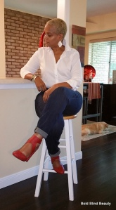 Blue cuffed skinny jeans, white button up, almond toe pumps (red chunky heels) with criss-cross ankle strap, silver cuff bracelet and 2 inch silver diamond shaped lace-like earrings. I'm stitting cross legged on my bar stool looking towards the counter away from the camera for a three-quarter view.
