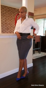 Gray pencil skirt, Standing with right arm on the counter facing forward.