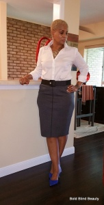 Gray pencil skirt. Standing with right hand touching the counter facing the left.