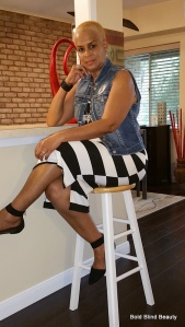 Black & white striped tank midi dress, blue denim vest, pointed black flats with ankle strap, black stretch cuff bracelet, silver & black pendant and silver hoop earrings. I'm sittingcross-legged on my barstool leaning one arm on the counter.