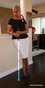 Frontal standing pose with white cane leaning on right arm against counter.