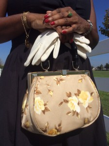 This photo is a close up of the cream colored floral vintage handbag and white gloves