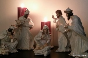 Ceramic nativity scene with two pillar candles providing illumination