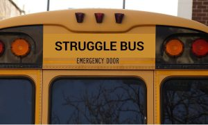 Rear of yellow school bus with the words Struggle Bus above the emergency door.