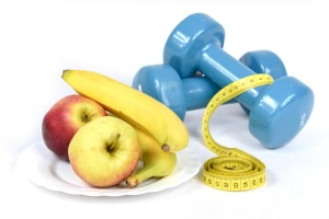 2 bananas & 2 apples on a dish next to 2 hand weights and a body tape measure