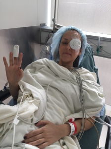 Nicole is waving to the camera from her hospital bed in recovery on Feb. 1, 2017 right after the vitrectomy of her left eye.