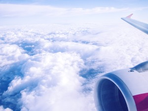 Jet engine and partial wing high above a bed of puffy white clouds.