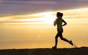 Image is of a woman running during a hazy golden sunrise.