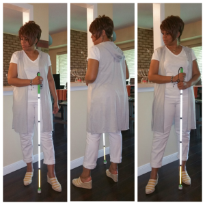White tee, white jeans, striped yellow & white wedges, long gray hooded vest and white cane.