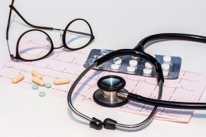 Stethoscope, eyeglasses, packet of pills, loose pills and capsules, laying atop a EKG report